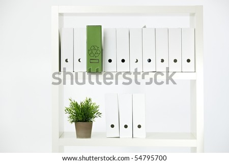 Conceptual image of environmental conservation, green folder with recycling symbol on a shelf full of white folders. - stock photo