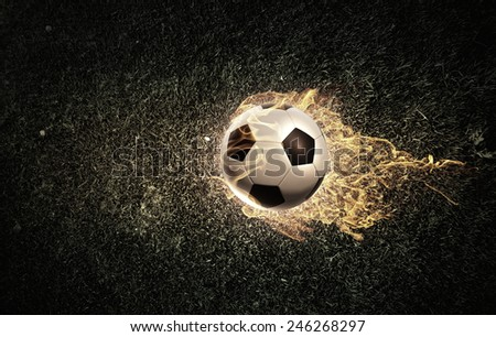 Conceptual image of football ball in fire flames - stock photo