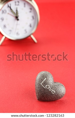 Conceptual image of heart with clock in background. Extreme shallow depth of field with selective focus on foreground. - stock photo