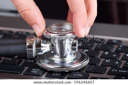 Conceptual image of male hand holding stethoscope on keyboard of laptop - stock photo
