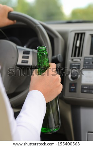 Conceptual image of the hand of a woman drinking alcohol and driving holding a green glass bottle of liquor in her hand as she steers the car - stock photo