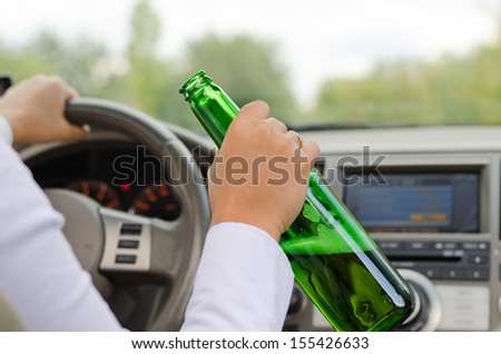 Conceptual image of the hand of an alcoholic female driving a car steering with one hand on the wheel and holding a bottle of booze in the other - stock photo