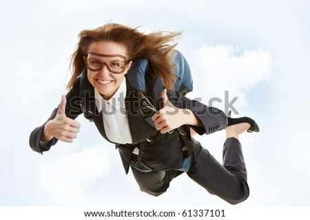 Conceptual image of young female flying with parachute and showing thumbs up - stock photo