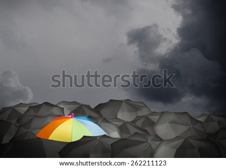 Conceptual image with colorful umbrella among many black ones - stock photo