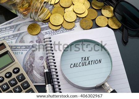 Conceptual image with hundred dollar bills, coins, calculator, notepad and magnifying glass with word Tax Calculation. - stock photo