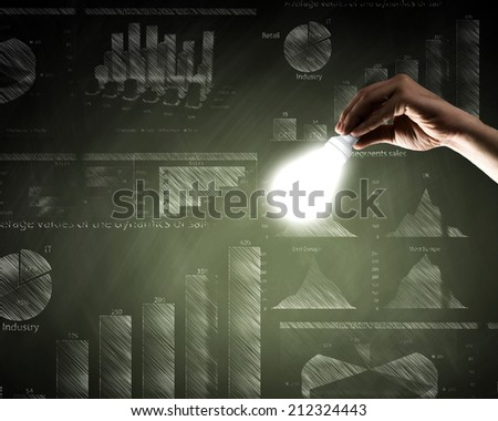 Conceptual image with light bulb diagrams and graphs - stock photo