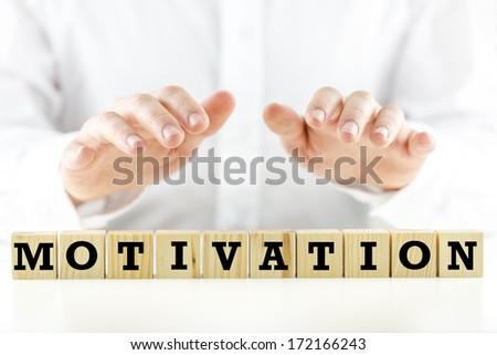 Conceptual image with the word Motivation on wooden blocks or cubes protected by the hands of a man sheltering them from above - stock photo