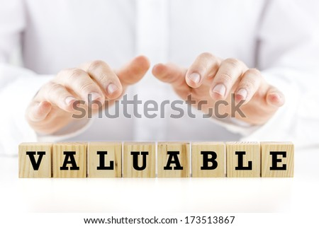 Conceptual image with the word - Valuable- on a row of natural wooden cubes or blocks with a man holding his hands cupped protectively over the top shielding them - stock photo