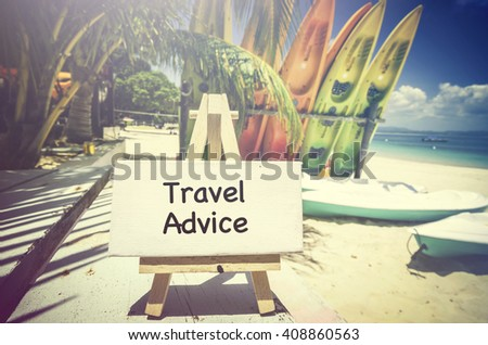conceptual image with word TRAVEL ADVICE on white canvas frame and wooden tripod. Blurred image of beach and colorful kayaks background. - stock photo
