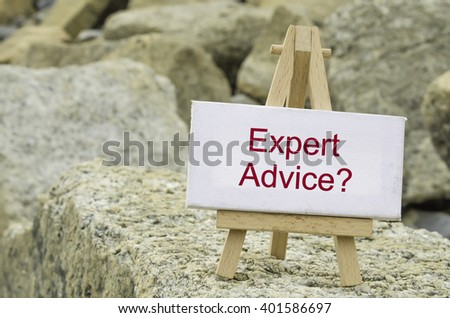 conceptual image,  word EXPERT ADVICE on white canvas frame and wooden tripod stand.blur rock textures background - stock photo