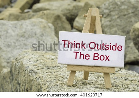 conceptual image,  word THINK OUTSIDE THE BOX on white canvas frame and wooden tripod stand.blur rock textures background - stock photo