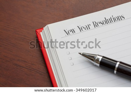 Conceptual,notebook on a wooden table. open diary and pen with new year resolutions words - stock photo