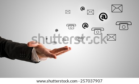 Conceptual One Open Businessman Hand with At, Telephone and Mail Symbols on Gray Gradient Background. - stock photo