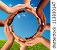 Conceptual peace and cultural diversity symbol of multiracial hands making a circle together on blue sky and green grass background. - stock photo