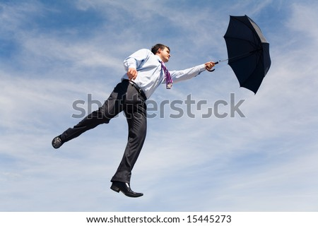 Conceptual photo of businessman flying on his umbrella up into bright blue sky - stock photo