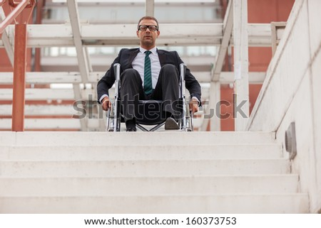 Conceptual photo of businessman on wheelchair in front of stairs - stock photo