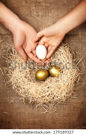 Conceptual photo of men and women hands putting white egg to nest with two golden eggs - stock photo