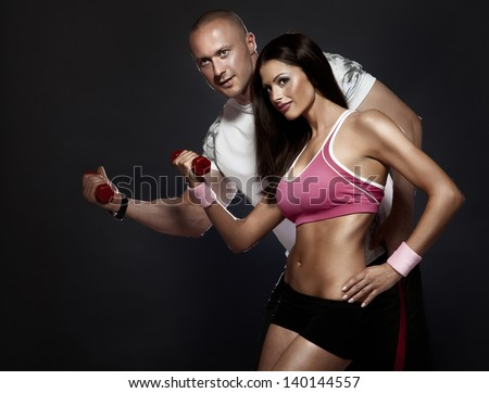 Conceptual photo of very attractive couple with perfect fitness body at the gym. Beautiful woman, handsome man. - stock photo