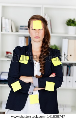 Conceptual photograph of a female showing lots of work pressure with sticky notes glued all over her body. - stock photo