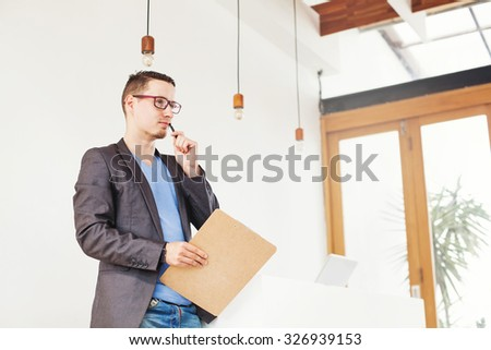 conceptual portrait of a man thinking of new ideas for business in office interior - stock photo