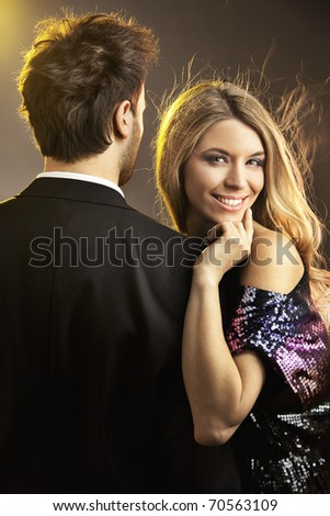 Conceptual portrait of a young couple in elegant evening dresses - stock photo