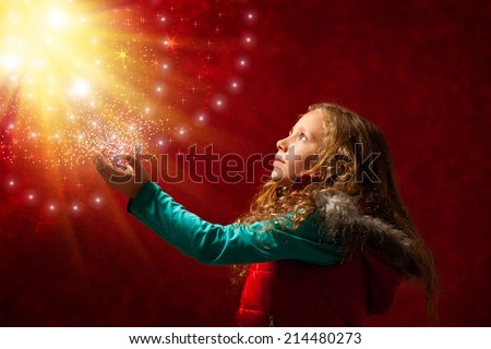 Conceptual portrait of cute young girl touching the stars against reddish galaxy background. - stock photo