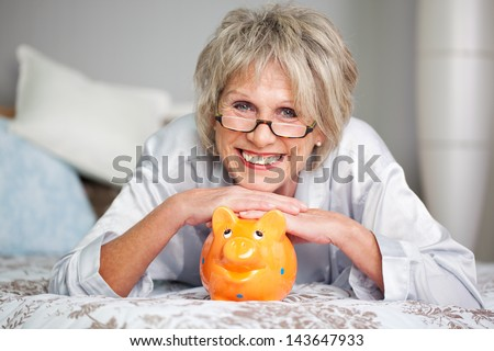 Conceptual portrait of happy senior female lying on bed with piggybank - stock photo