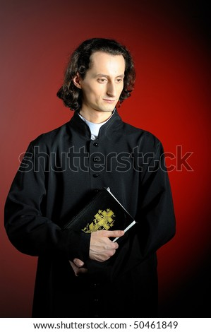conceptual portrait of Praying priest with  Holy Bible. red background - stock photo