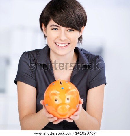 Conceptual portrait of smiling woman showing an orange piggybank - stock photo