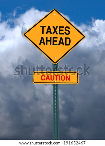 conceptual post sign caution taxes ahead sign over dramatic sky - stock photo