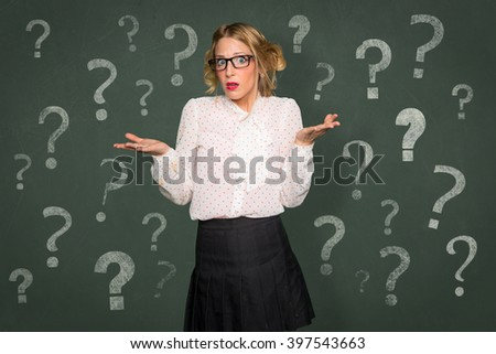 Conceptual question mark symbol confused baffled overwhelmed helpless woman nerdy classroom chalkboard - stock photo
