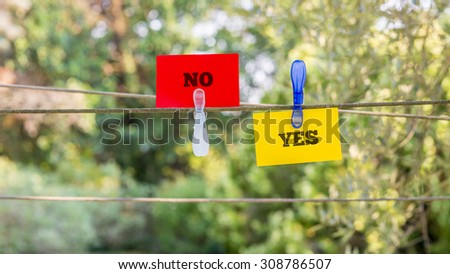 Conceptual Red and Yellow Paper with Yes and No Messages Clipped on a String Against Fuzzy Greenery Background. - stock photo