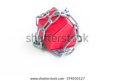 Conceptual red house locked with chain on white background - stock photo