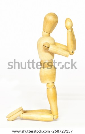Conceptual representation of praying with wooden mannequin - stock photo