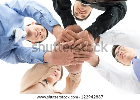 Conceptual shot of a dedicated business team joining hands - stock photo