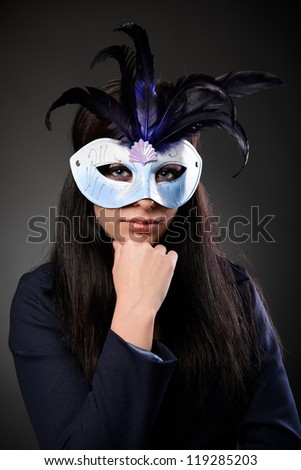 Conceptual shot of a mysterious businesswoman wearing feathered mask - stock photo