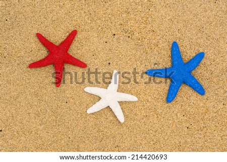 Conceptual summer holiday image of three red, white and blue starfish on smooth sand representing patriotism and the Fourth of July holiday. - stock photo