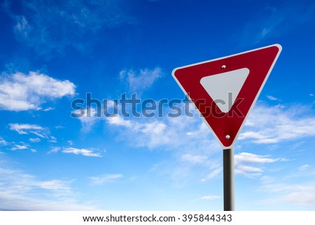 Conceptual yield sign against a blue cloudy sky. - stock photo