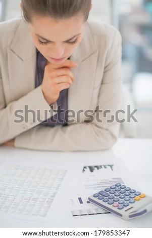 Concerned business woman working with documents - stock photo