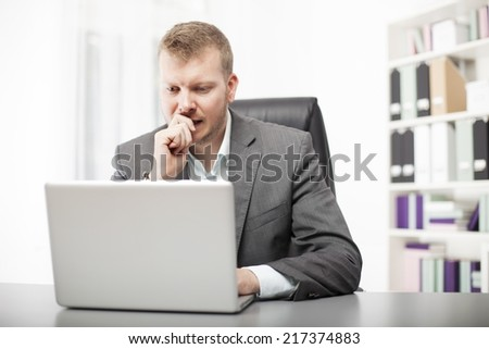 Concerned businessman working at his desk in the office staring at the screen of his laptop computer with a worried expression - stock photo
