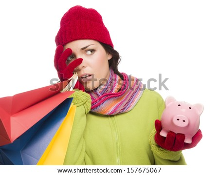Concerned Expressive Mixed Race Woman Wearing Winter Clothing Holding Shopping Bags and Piggy Bank Isolated on White Background. - stock photo