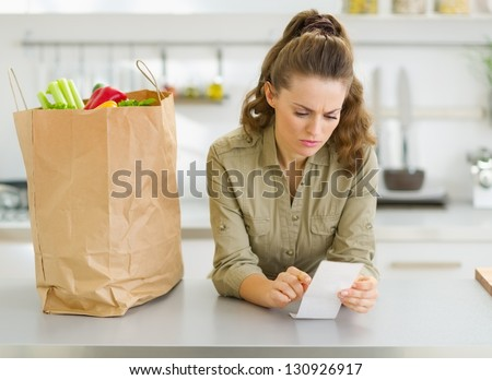 Concerned housewife checking bill after shopping in kitchen - stock photo
