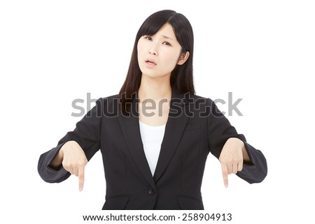 concerned Japanese businesswoman pointing down - stock photo