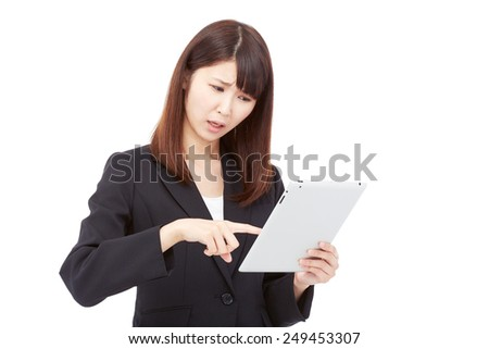 concerned Japanese businesswoman with the tablet - stock photo