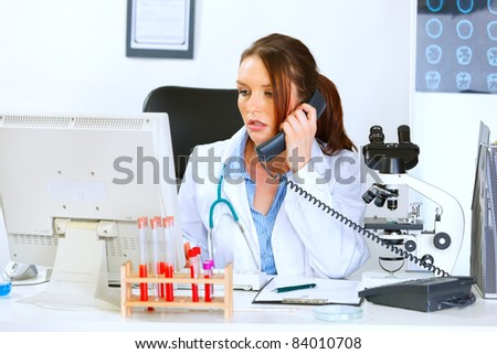 Concerned medical doctor woman talking on phone and looking in monitor - stock photo
