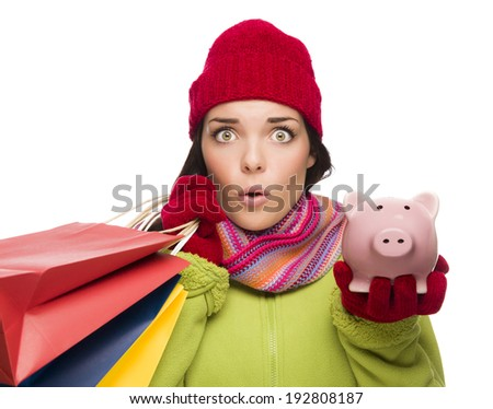 Concerned Mixed Race Woman Wearing Winter Clothes Holding Shopping Bags and Piggy Bank Isolated on White Background. - stock photo