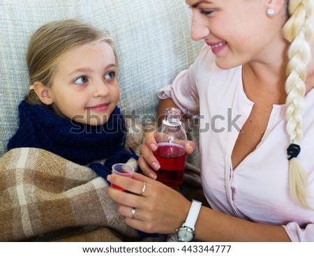 Concerned mother giving mixture to daughter with cough - stock photo