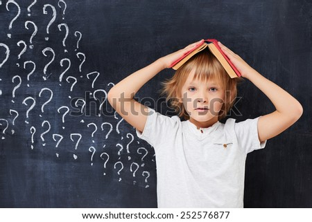 Concerned redhead pupil desperate by a large number of question - stock photo