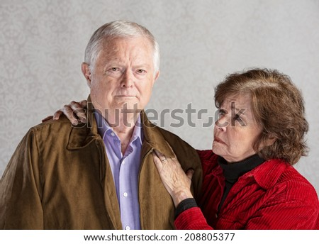 Concerned senior husband and wife over gray background - stock photo