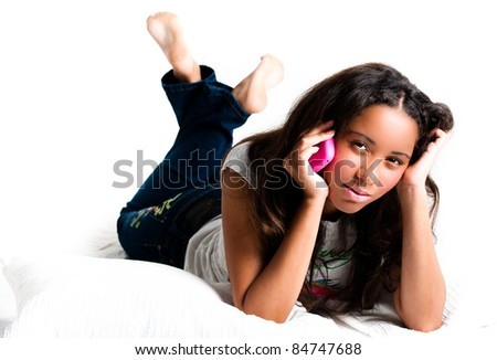Concerned teenage girl on a pink cell phone lying down listening with legs crossed feet in the air - isolated on white - stock photo